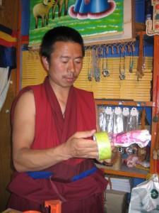 Monk wrapping prayer wheel